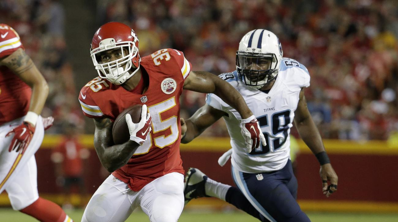 Kansas City Chiefs running back Charcandrick West (35) runs from Tennessee Titans linebacker Wesley Woodyard (59) during the second half of a preseason NFL football game at Arrowhead Stadium in Kansas City, Mo., Friday, Aug. 28, 2015. (AP Photo/Charlie Ri