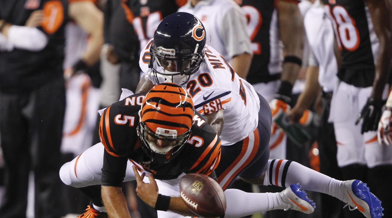 Cincinnati Bengals quarterback AJ McCarron (5) fumbles the ball out of bounds as he is tackled by Chicago Bears cornerback Terrance Mitchell (20) during the first half of an NFL preseason football game, Saturday, Aug. 29, 2015, in Cincinnati. (AP Photo/Fr
