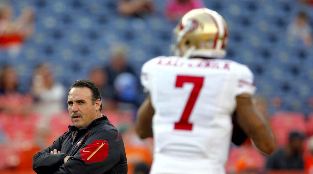 San Francisco 49ers coach Jim Tomsula watches quarterback Colin Kaepernick (7) warm up for an NFL preseason football game against the Denver Broncos, Saturday, Aug. 29, 2015, in Denver. (AP Photo/Joe Mahoney)