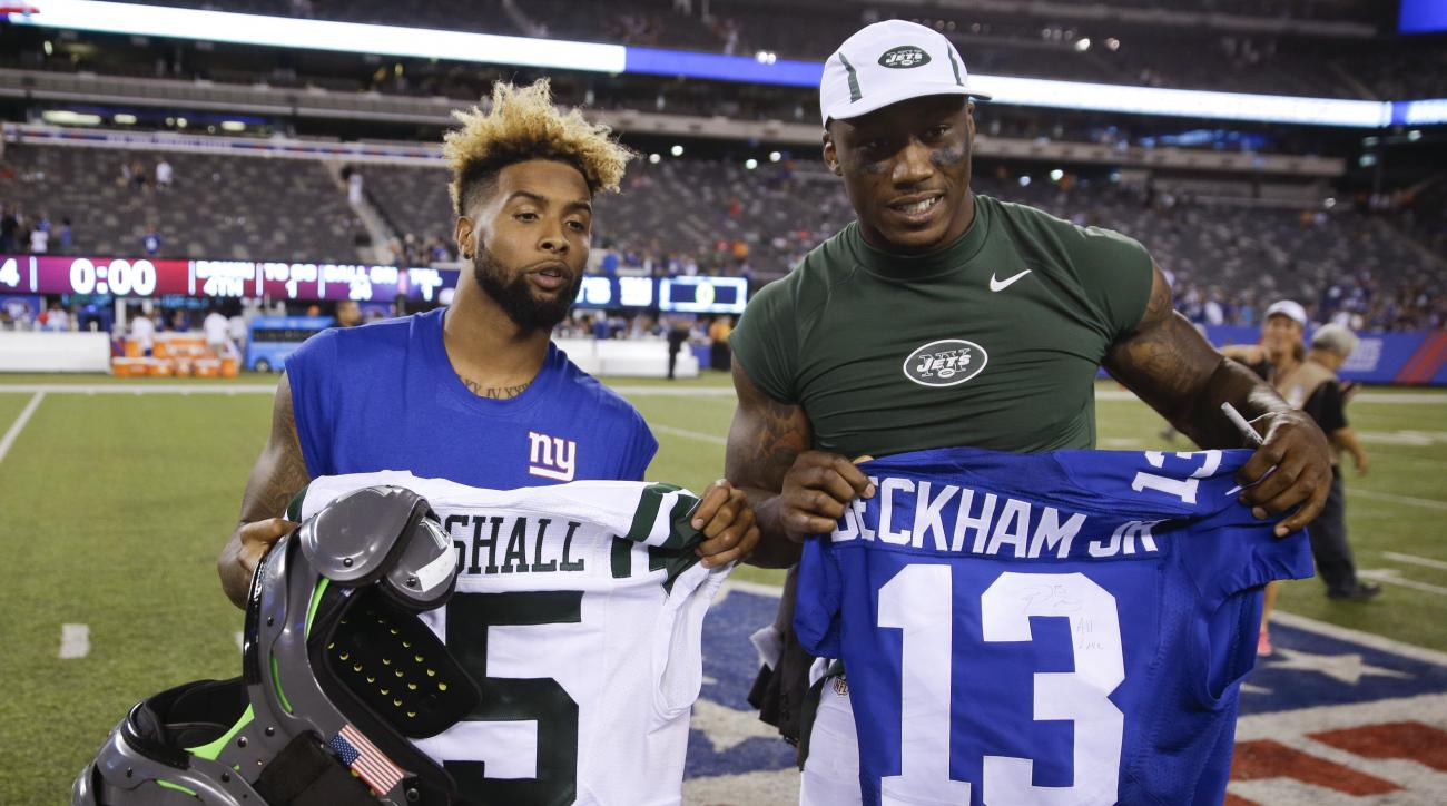 New York Giants wide receiver Odell Beckham, left, and New York Jets wide receiver Brandon Marshall, right, pose for photographs after exchanging jerseys after a preseason NFL football game Saturday, Aug. 29, 2015, in East Rutherford, N.J. The Jets won 28