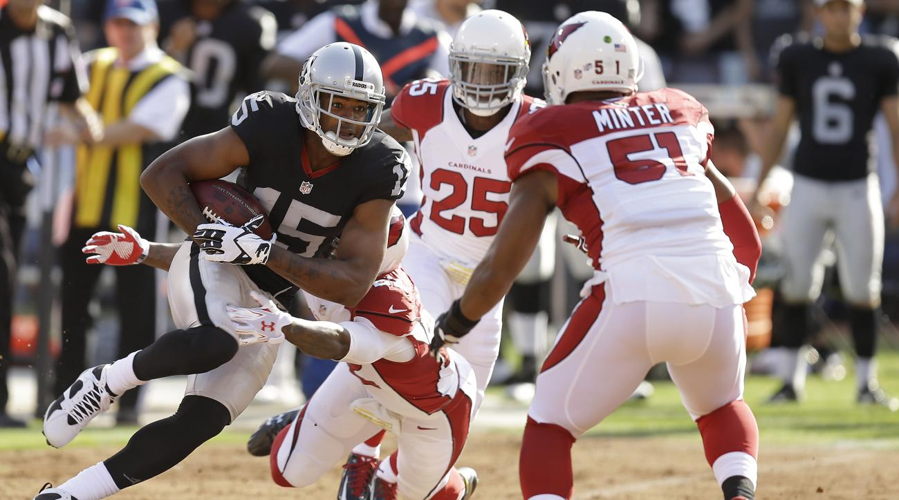 Oakland Raiders wide receiver Michael Crabtree (15) is tackled by Arizona Cardinals defensive back Tony Jefferson, bottom, while under pressure from cornerback Jerraud Powers (25) and linebacker Kevin Minter (51) during the first half of an NFL preseason