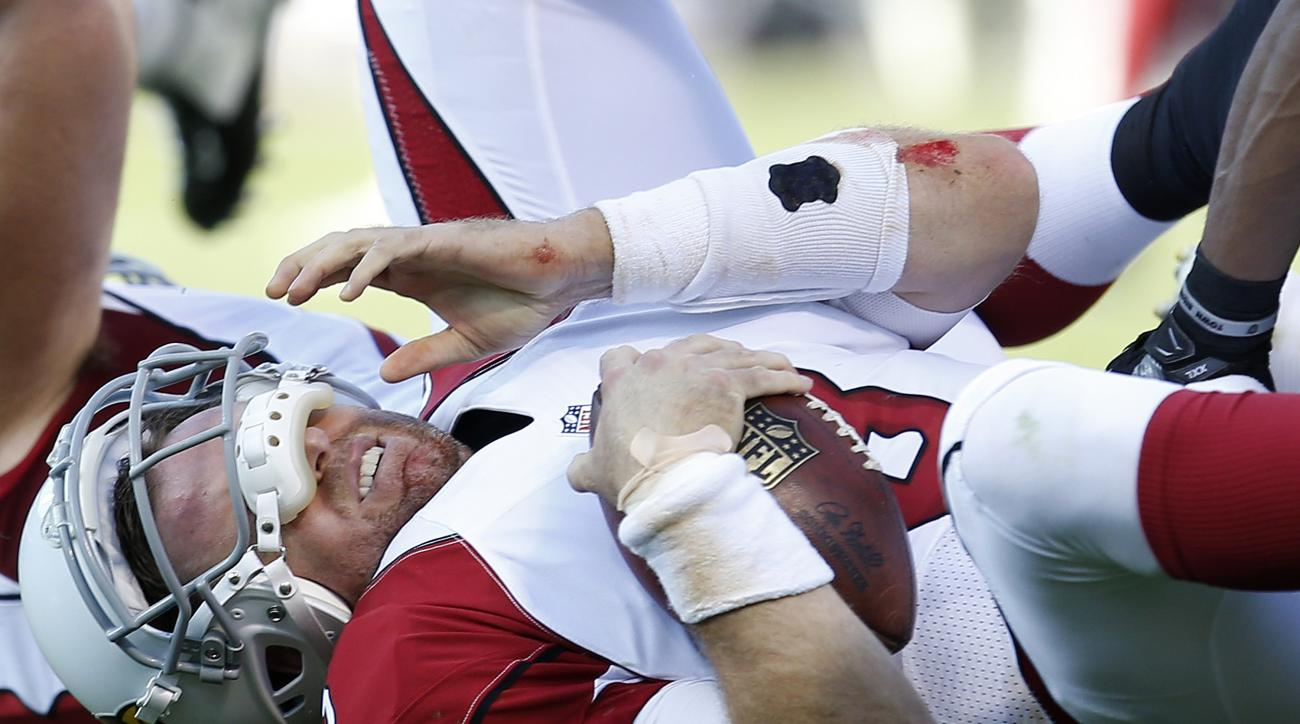 Arizona Cardinals quarterback Carson Palmer (3) rests on the ground after being sacked by Oakland Raiders outside linebacker Khalil Mack during the first half of an NFL preseason football game in Oakland, Calif., Sunday, Aug. 30, 2015. (AP Photo/Tony Avel