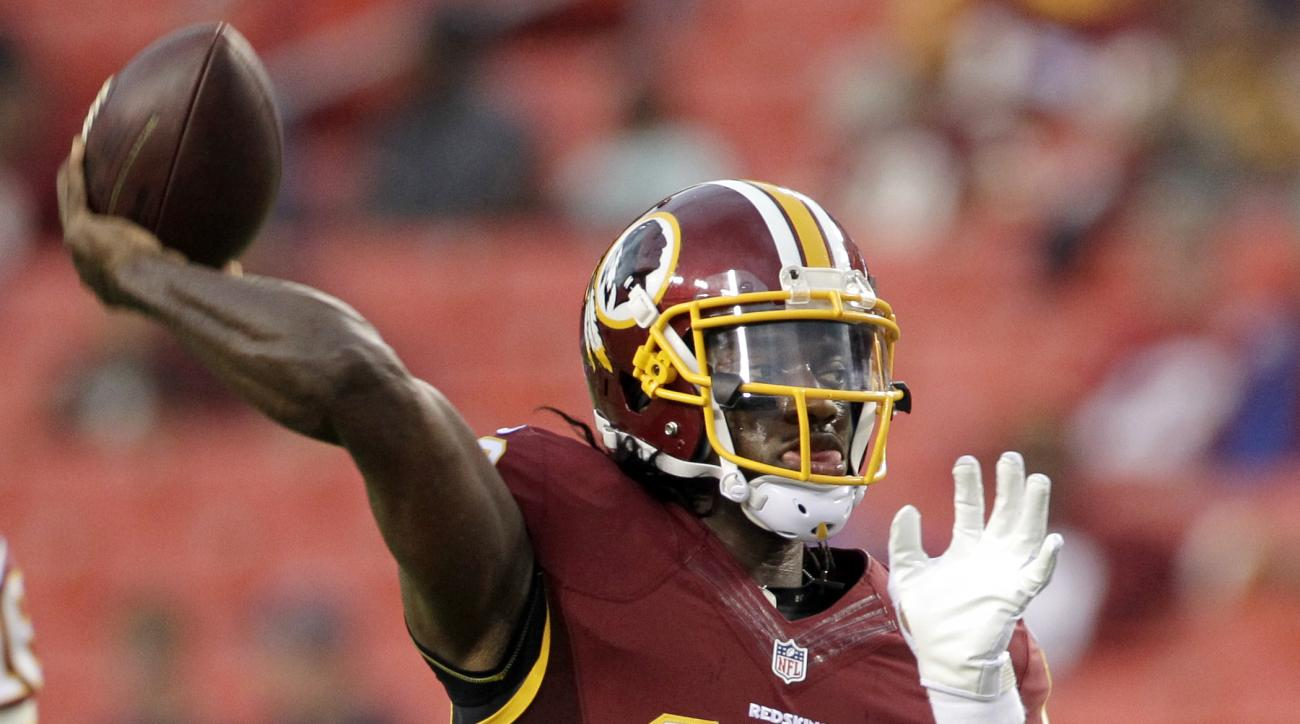 FILE - In this Aug. 20, 2015 file photo, Washington Redskins quarterback Robert Griffin III warms up before an NFL preseason football game against the Detroit Lions, in Landover, Md. Kirk Cousins will start the season as Washington's quarterback, Redskins