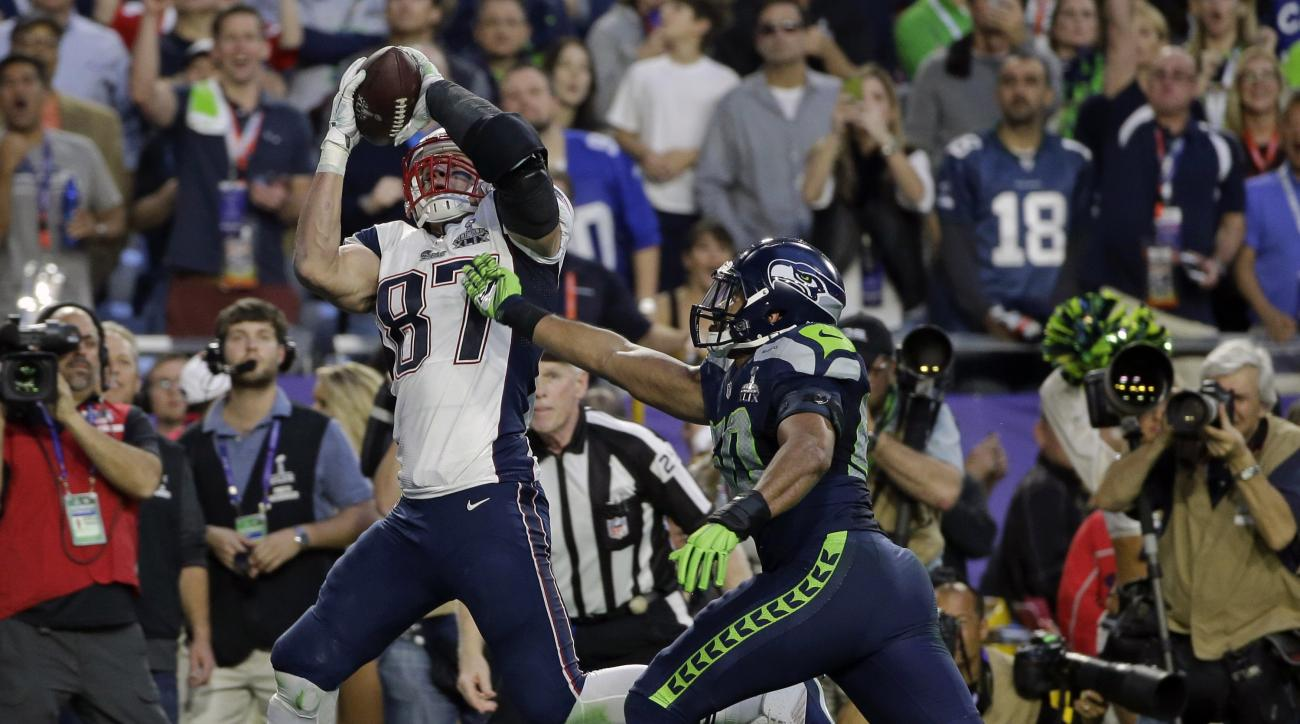 FILE - In this Sunday, Feb. 1, 2015 file photo, New England Patriots tight end Rob Gronkowski (87), left, hauls in a touchdown pass ahead of Seattle Seahawks outside linebacker K.J. Wright (50) during the first half of NFL Super Bowl XLIX football game in