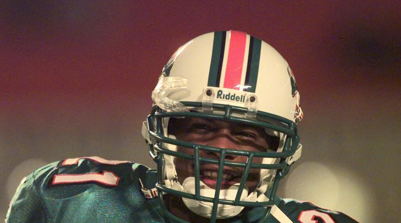 Lawerence Phillips smiles as the crowd in the stands at Pro Player Stadium calls out to him as he takes the field for the first time in a Miami Dolphins uniform Sunday Dec. 7, 1997 in Miami before a game against the Detroit Lions. Phillips signed with the