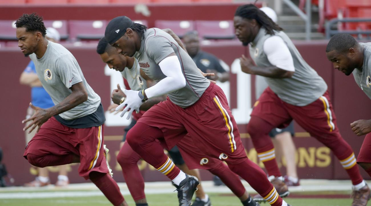 Washington Redskins quarterback Robert Griffin III, center, warms up with teammates before an NFL preseason football game against the Jacksonville Jaguars in Landover, Md., Thursday, Sept. 3, 2015. (AP Photo/Alex Brandon)