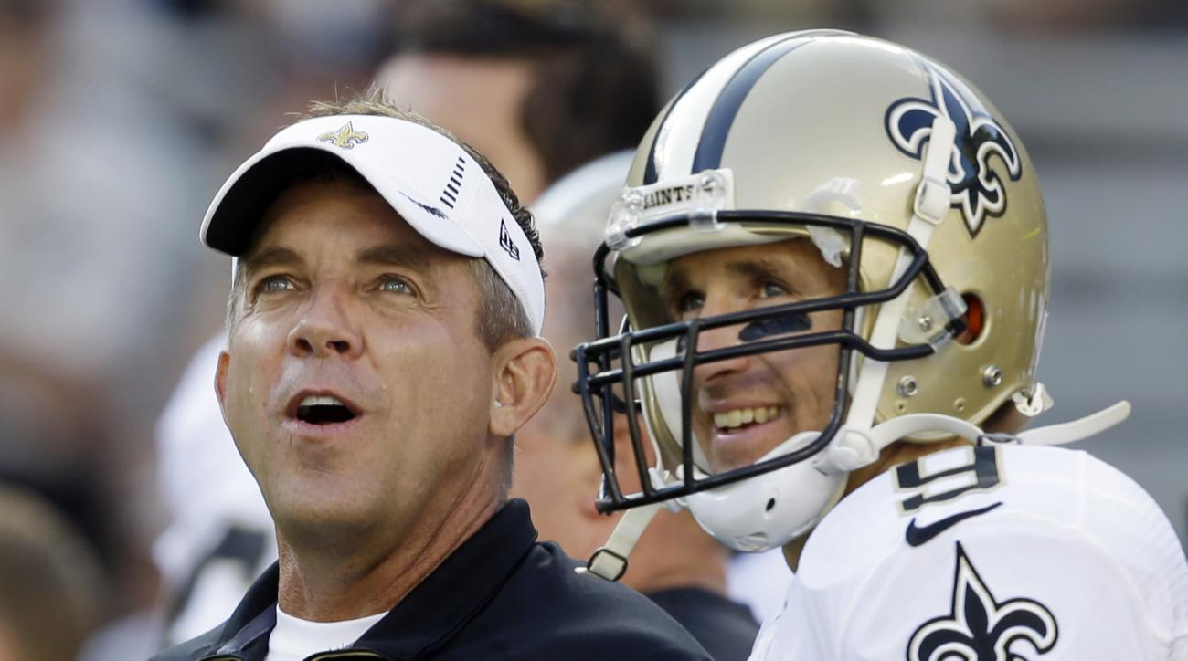 New Orleans Saints head coach Sean Payton talks to quarterback Drew Brees before a preseason NFL football game against the Green Bay Packers Thursday, Sept. 3, 2015, in Green Bay, Wis. (AP Photo/Jeffrey Phelps)