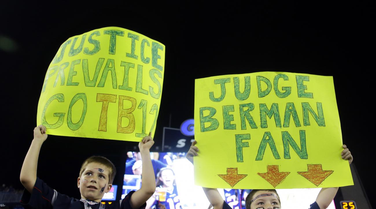 New England Patriots fans Luke, left, and Andrew Sheridan, of Hanover, Mass., hold signs referring to Federal Judge Richard M. Berman in the first half an NFL preseason football game between the Patriots and the New York Giants Thursday, Sept. 3, 2015, in