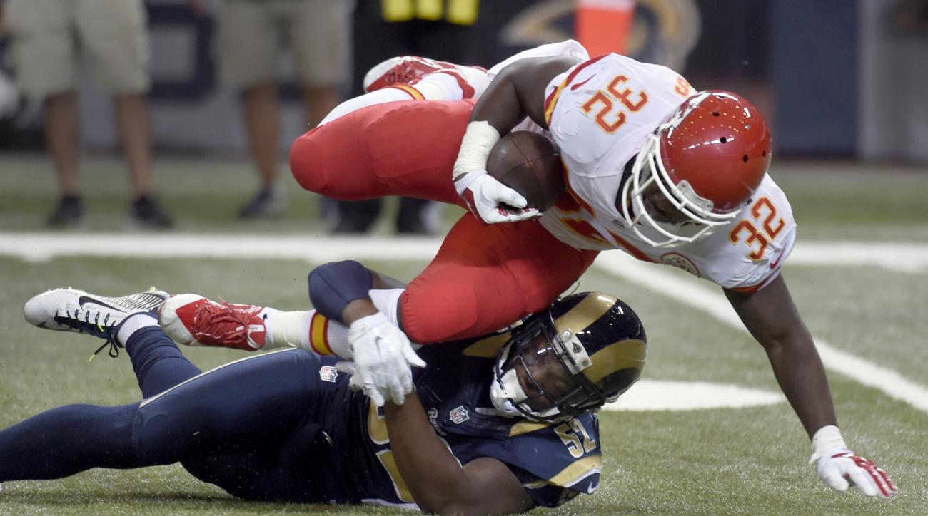 Kansas City Chiefs running back Darrin Reaves, top, struggles for yardage before being brought down by St. Louis Rams outside linebacker Alec Ogletree during the first quarter of an NFL preseason football game Thursday, Sept. 3, 2015, in St. Louis. (AP Ph