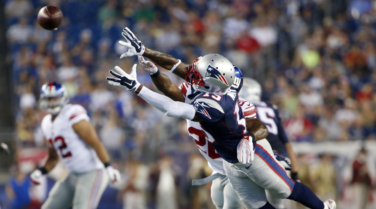 New England Patriots wide receiver Reggie Wayne (15) stretches but cannot catch a pass in the first half of an NFL football game as New York Giants cornerback Prince Amukamara defends Thursday, Sept. 3, 2015, in Foxborough, Mass. (AP Photo/Winslow Townson