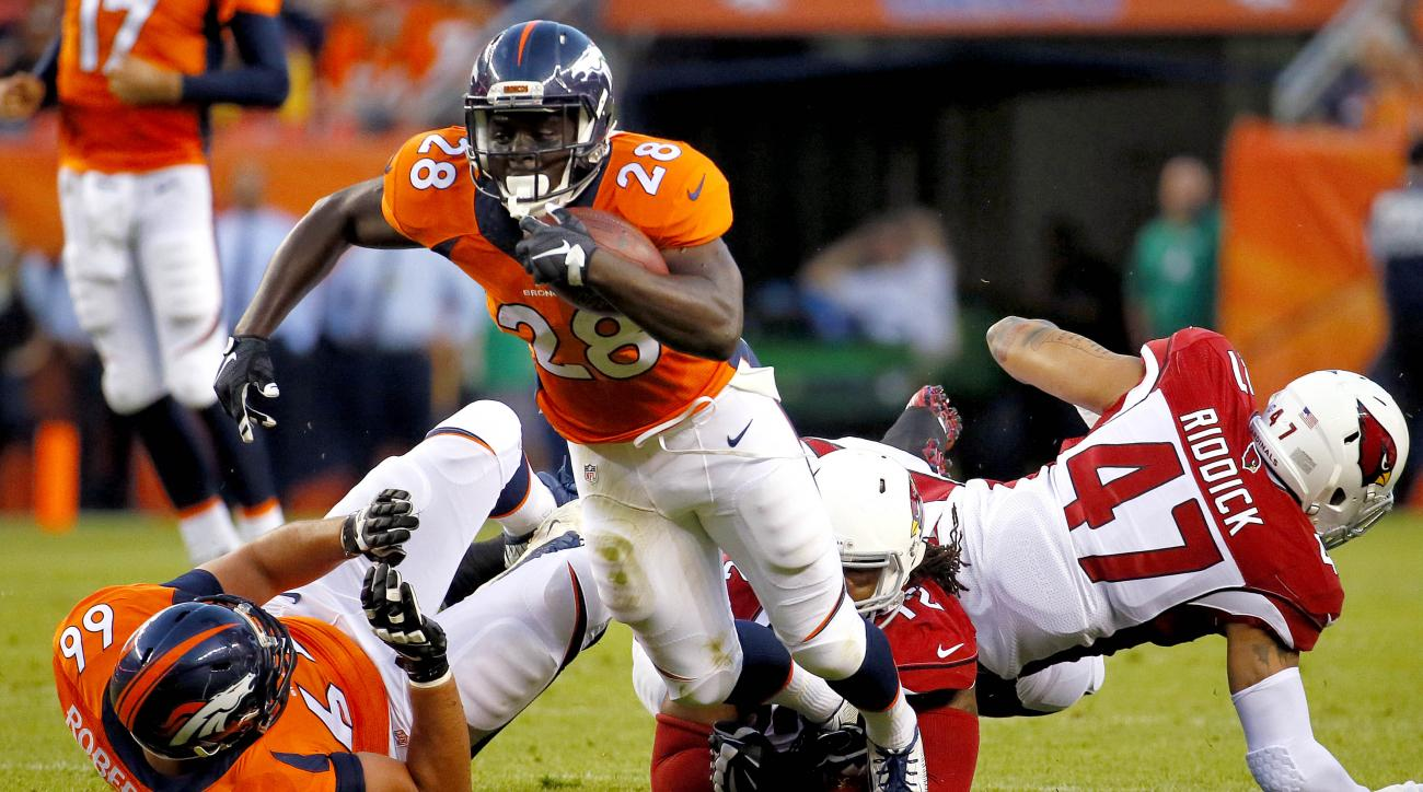 Denver Broncos running back Montee Ball (28) is tripped up by Arizona Cardinals defensive end Ed Stinson (72) during the first half of an NFL preseason football game, Thursday, Sept. 3, 2015, in Denver. (AP Photo/Jack Dempsey)