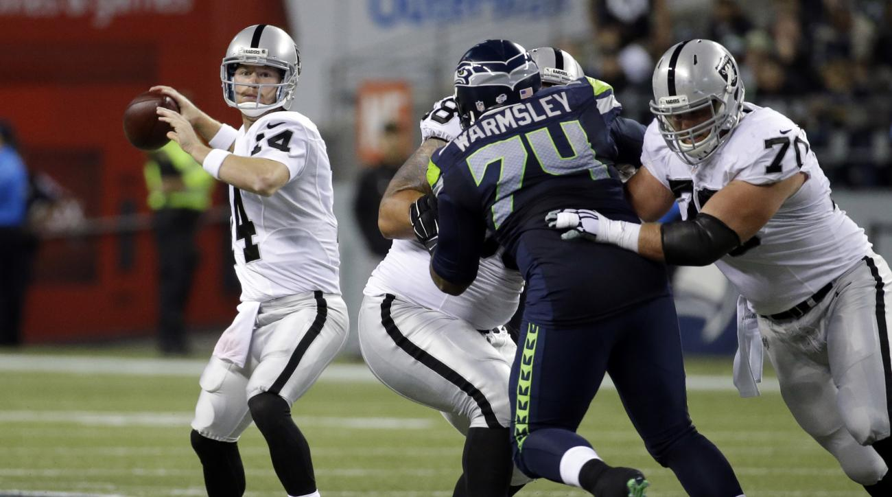 Oakland Raiders quarterback Matt McGloin (14), left passes as Seattle Seahawks defensive tackle Julius Warmsley (74) is blocked in the first half of a preseason NFL football game, Thursday, Sept. 3, 2015, in Seattle. (AP Photo/Elaine Thompson)