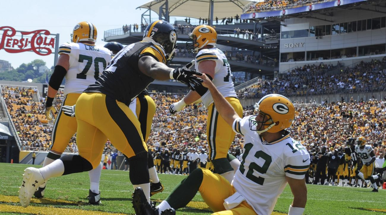 FILE- In this Aug. 23, 2015, file photo, Pittsburgh Steelers outside linebacker James Harrison (92) helps up Green Bay Packers quarterback Aaron Rodgers (12) during the NFL pre-season football game in Pittsburgh. Harrison, now a decidedly older player tha