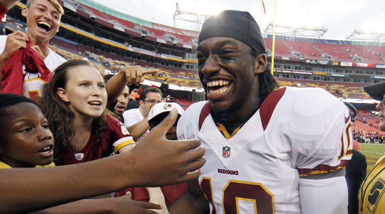 FILE - In This Aug. 25, 2012, file photo, Washington Redskins quarterback Robert Griffin III smiles as he greets fans after an NFL preseason football game against the Indianapolis Colts in Landover, Md. Griffin and Indianapolis Colts quarterback Andrew Lu