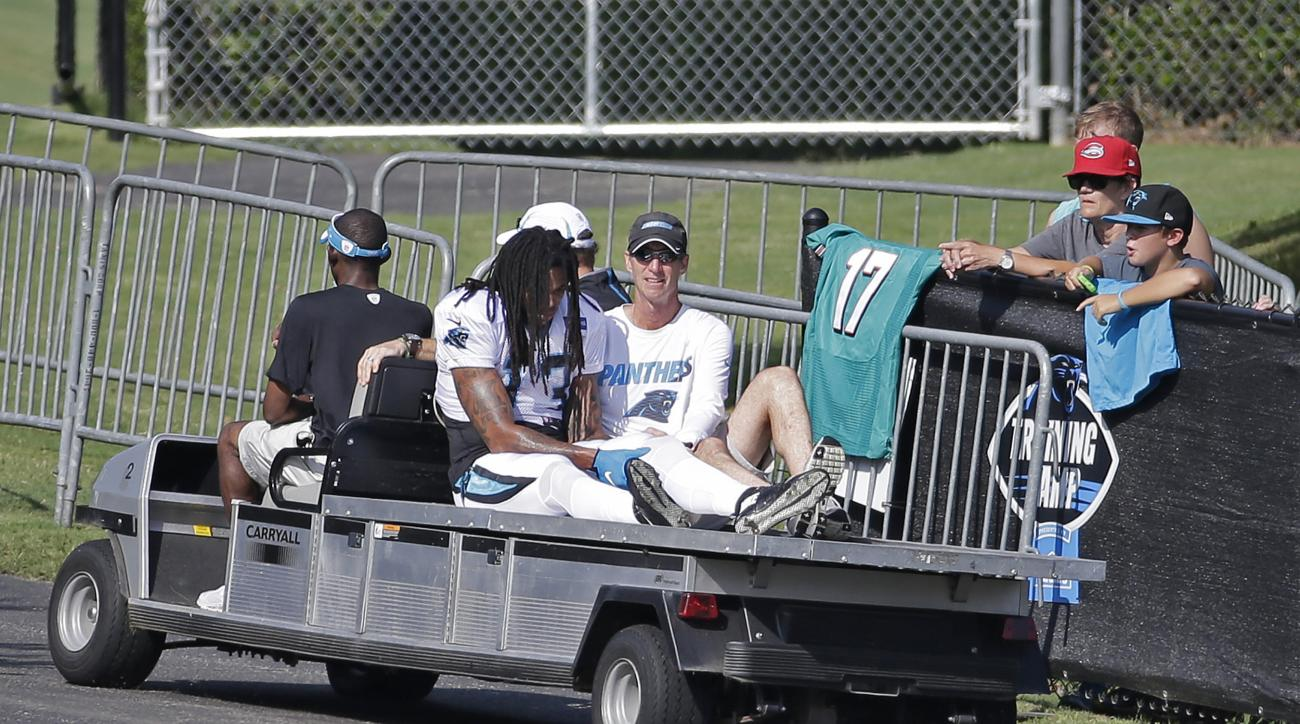 FILE - In this Aug. 19, 2015, file photo, Carolina Panthers' Kelvin Benjamin (13) holds his left knee as he is carted off the field after being injured during a joint practice with the Miami Dolphins at NFL football training camp in Spartanburg, S.C. As t