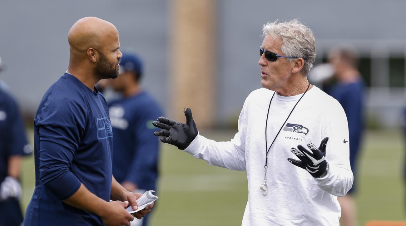 FILE - In this June 18, 2015, file photo, Seattle Seahawks head coach Pete Carroll, right, talks with defensive coordinator Kris Richard, left, during NFL football minicamp in Renton, Wash. Under the watchful eye of Carroll, the Seahawks defense has devel