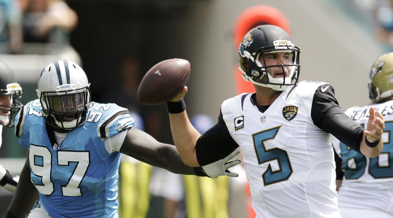 Jacksonville Jaguars quarterback Blake Bortles (5) looks for a receiver as Carolina Panthers defensive end Mario Addison (97) puts on pressure during the first half of an NFL football game in Jacksonville, Fla., Sunday, Sept. 13, 2015. (AP Photo/John Raou