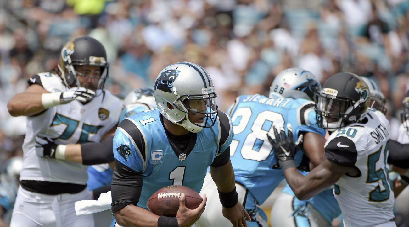 Carolina Panthers quarterback Cam Newton (1) runs for yardage between Jacksonville Jaguars defensive tackle Jared Odrick, left, and outside linebacker Telvin Smith (50) during the first half of an NFL football game in Jacksonville, Fla., Sunday, Sept. 13,