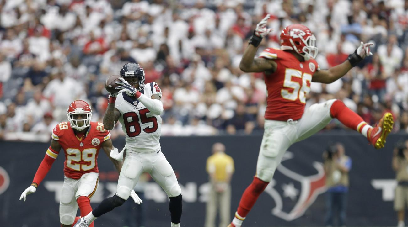 Houston Texans' Nate Washington (85) catches a pass between Kansas City Chiefs defenders Eric Berry (29) and Derrick Johnson (56) during the first half of an NFL football game Sunday, Sept. 13, 2015, in Houston. (AP Photo/Patric Schneider)
