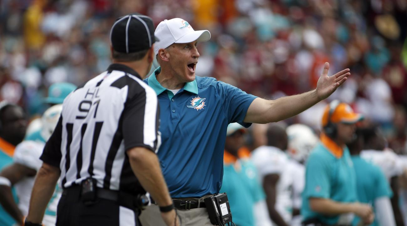 Head linesman Jerry Bergman, left, listens to Miami Dolphins head coach Joe Philbin during the first half of an NFL football game against the Washington Redskins, Sunday, Sept. 13, 2015, in Landover, Md. (AP Photo/Evan Vucci)