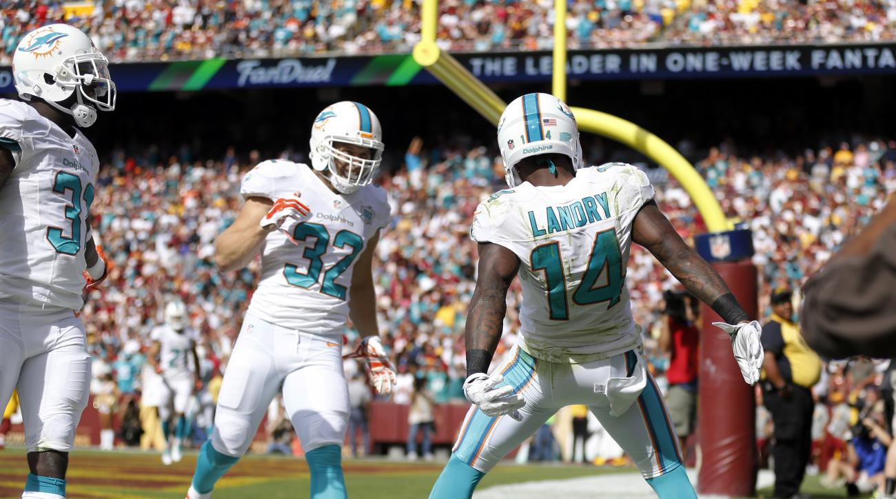 Miami Dolphins wide receiver Jarvis Landry (14) celebrates his touchdown with free safety Michael Thomas (31) and defensive back Jordan Kovacs (32) during the second half of an NFL football game against the Washington Redskins, Sunday, Sept. 13, 2015, in