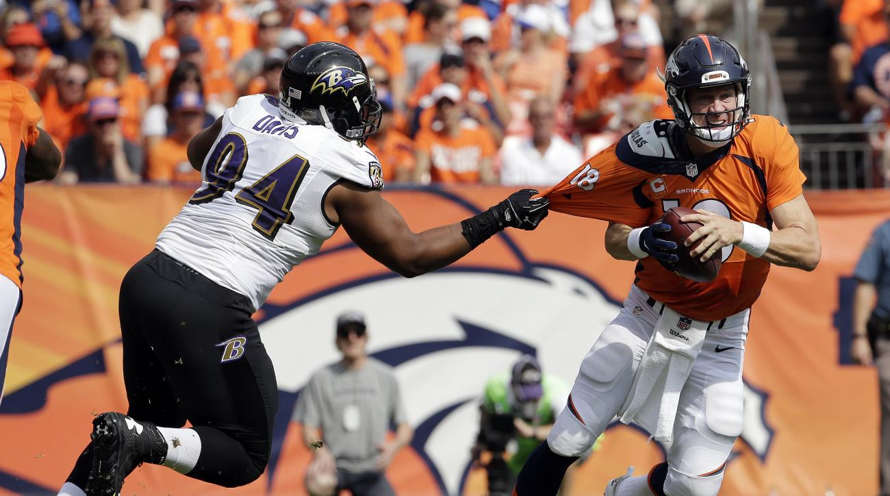 Baltimore Ravens defensive tackle Carl Davis, left, pulls on the jersey of Denver Broncos quarterback Peyton Manning during the first half of an NFL football game Sunday, Sept. 13, 2015, in Denver. (AP Photo/Jack Dempsey)