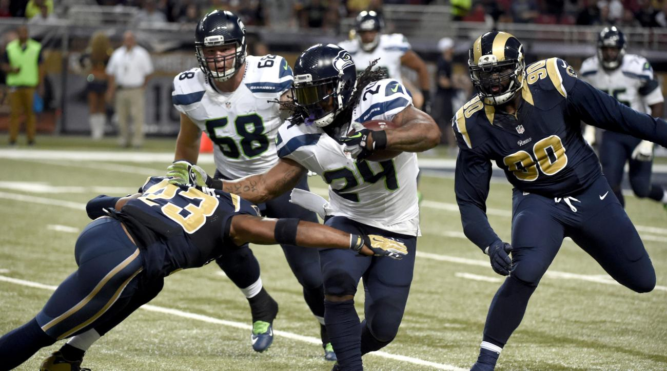 CORRECTS SEAHAWKS PLAYER TO OFFENSIVE TACKLE JUSTIN BRITT INSTEAD OF LINEBACKER KEVIN PIERRE-LOUIS -  Seattle Seahawks running back Marshawn Lynch (24) runs with the ball as St. Louis Rams free safety Rodney McLeod (23) and defensive tackle Michael Brocke