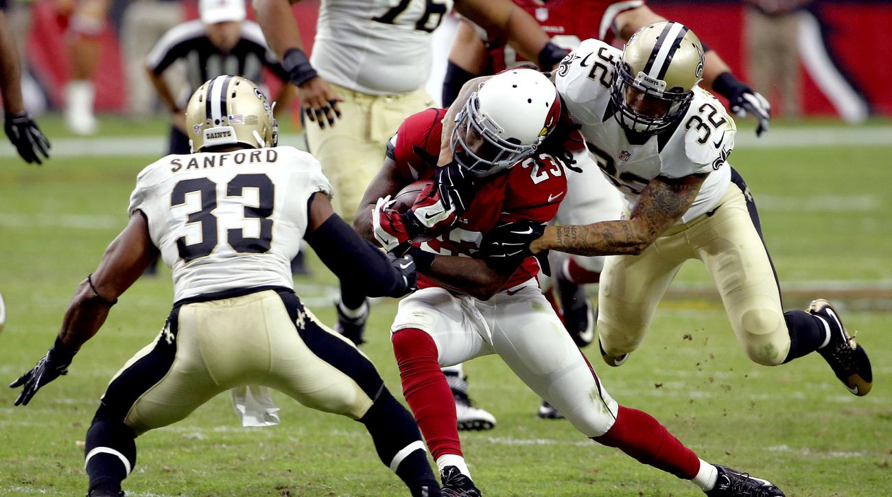 Arizona Cardinals running back Chris Johnson (23) his hit by New Orleans Saints strong safety Kenny Vaccaro (32) as strong safety Jamarca Sanford (33) defends during the second half of an NFL football game, Sunday, Sept. 13, 2015, in Glendale, Ariz. (AP P