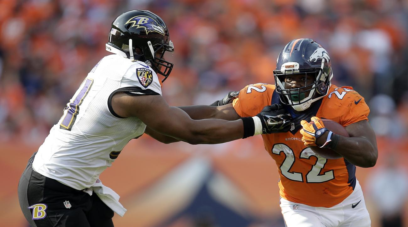 Denver Broncos running back C.J. Anderson, right, pushes away Baltimore Ravens inside linebacker Daryl Smith during the second half of an NFL football game Sunday, Sept. 13, 2015, in Denver. (AP Photo/Joe Mahoney)