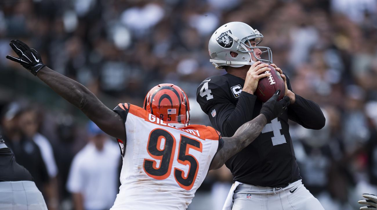 Oakland Raiders quarterback Derek Carr (4) throws an incomplete pass after being pressured by Cincinnati Bengals defensive end Wallace Gilberry (95) during an NFL football game in Oakland, Calif., Sunday, Sept. 13, 2015. (Paul Kitagaki Jr./The Sacramento