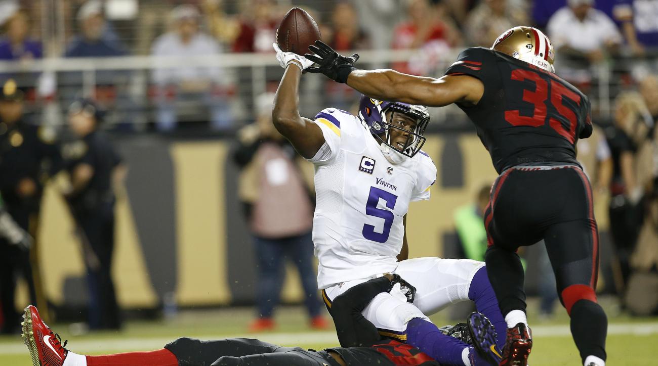 Minnesota Vikings quarterback Teddy Bridgewater (5) is sacked by San Francisco 49ers strong safety Jaquiski Tartt, bottom, as safety Eric Reid (35) follows during the first half of an NFL football game in Santa Clara, Calif., Monday, Sept. 14, 2015. (AP P