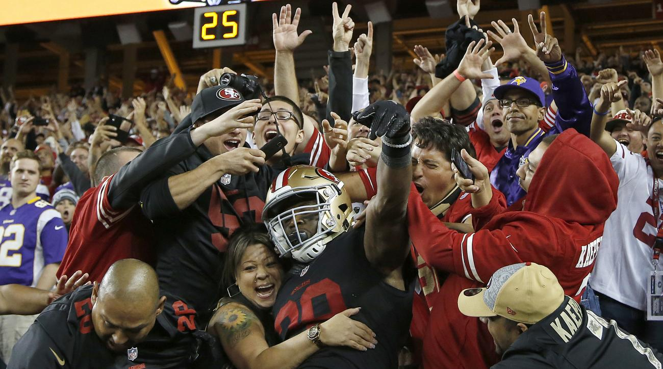San Francisco 49ers running back Carlos Hyde, center, celebrates with fans after scoring on a 17-yard touchdown run against the Minnesota Vikings during the second half of an NFL football game in Santa Clara, Calif., Monday, Sept. 14, 2015. (AP Photo/Tony