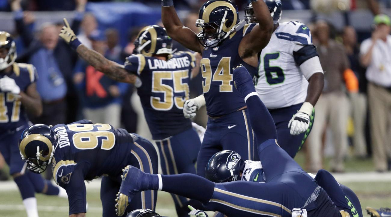 FILE - In this Sunday, Sept. 13, 2015 file photo, Seattle Seahawks running back Marshawn Lynch, bottom, lands on his back after being stopped on fourth down as St. Louis Rams players celebrate on the final play in overtime of an NFL football game in St. L