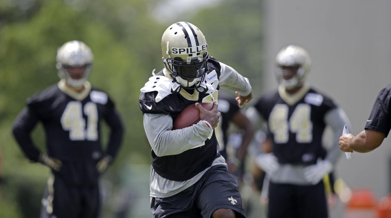 FILE - In this June 16, 2015, file photo, New Orleans Saints running back C.J. Spiller runs through drills during an NFL football minicamp in Metairie, La. Spiller says he isn't being coy when he declines to pinpoint when he'll play in his first game this