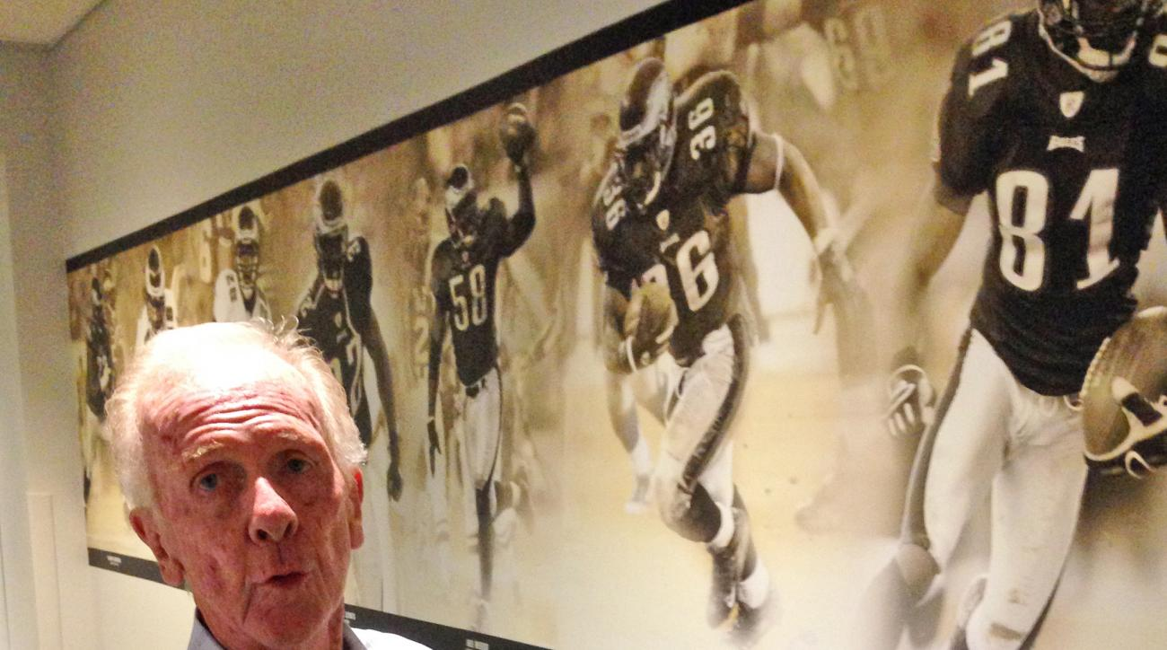 In this photo taken Thursday, Sept. 17, 2015, Leo Carlin, who recently retired after 55 years as the Philadelphia Eagles ticket manager, points to a picture of Terrell Owens as he walks through a hallway at the team's NFL football practice facility in Phi