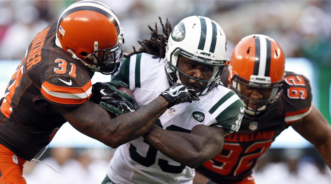FILE - In this Sunday, Sept. 13, 2015, file photo, New York Jets running back Chris Ivory (33) is tackled by Cleveland Browns' Donte Whitner (31) during the second half of an NFL football game in East Rutherford, N.J. The  Jets running back is a powerful,