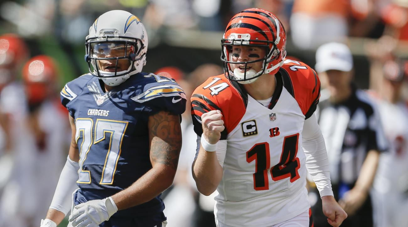 Cincinnati Bengals quarterback Andy Dalton (14) passes San Diego Chargers defensive back Jimmy Wilson (27) as he pumps his first while celebrating a touchdown by wide receiver A.J. Green, not pictured, in the first half of an NFL football game, Sunday, Se