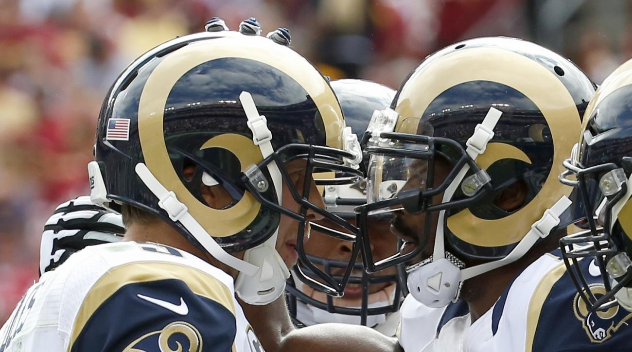St. Louis Rams quarterback Nick Foles (5) and wide receiver Kenny Britt (18) celebrate Britt's touchdown during the second half of an NFL football game against the Washington Redskins in Landover, Md., Sunday, Sept. 20, 2015. (AP Photo/Alex Brandon)