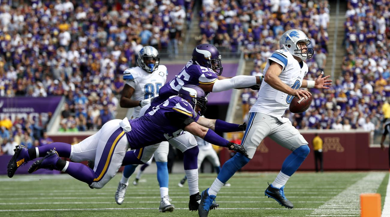 Detroit Lions quarterback Matthew Stafford (9) is pushed out of bounds by Minnesota Vikings defensive end Brian Robison (96) and linebacker Anthony Barr (55) in the second half of an NFL football game in Minneapolis, Sunday, Sept. 20, 2015. (AP Photo/Jim