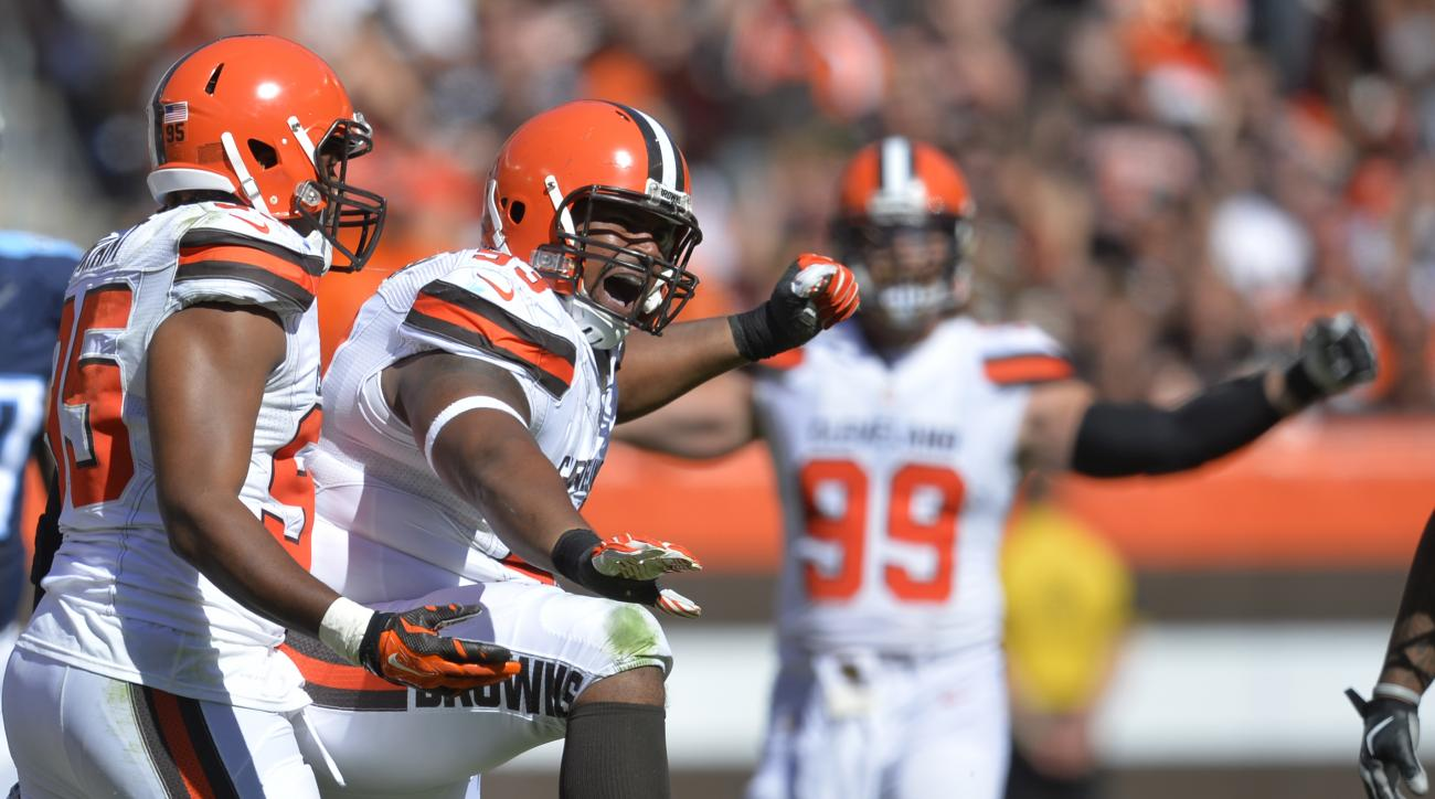 Cleveland Browns defensive end John Hughes, second from left, celebrates after sacking Tennessee Titans quarterback Marcus Mariota in the second half of an NFL football game Sunday, Sept. 20, 2015, in Cleveland. (AP Photo/David Richard)