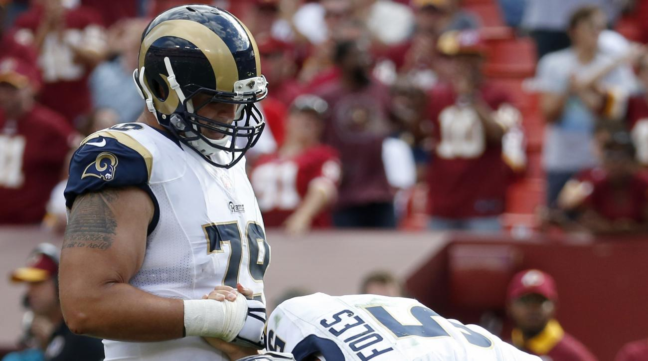St. Louis Rams quarterback Nick Foles (5) holds his leg as offensive tackle Rob Havenstein (79) helps him up during the second half of an NFL football game against the Washington Redskins in Landover, Md., Sunday, Sept. 20, 2015. Foles was injured in the