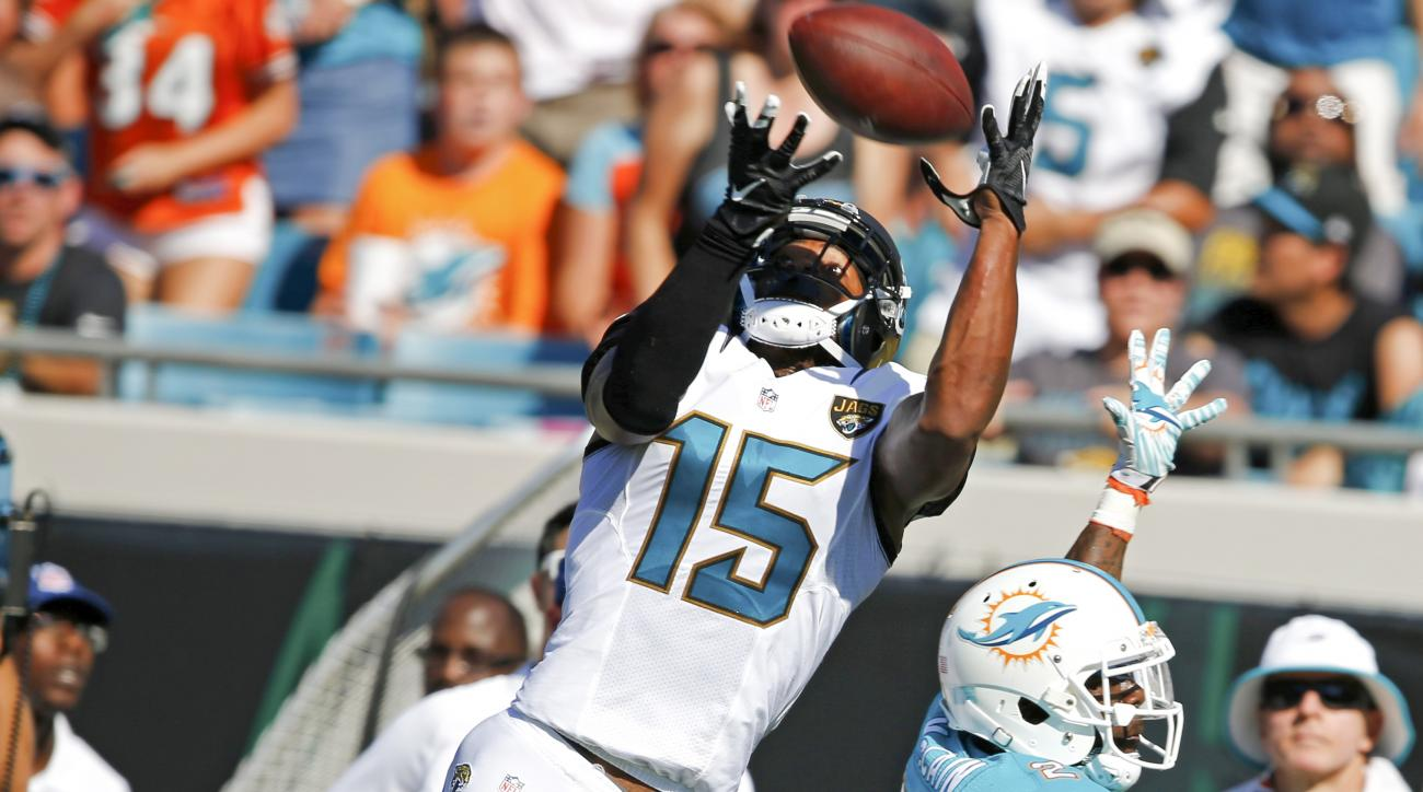 Jacksonville Jaguars wide receiver Allen Robinson (15) goes up for a catch as he is defended by Miami Dolphins cornerback Brice McCain, right, during the first half of an NFL football game in Jacksonville, Fla., Sunday, Sept. 20, 2015.(AP Photo/Stephen B.