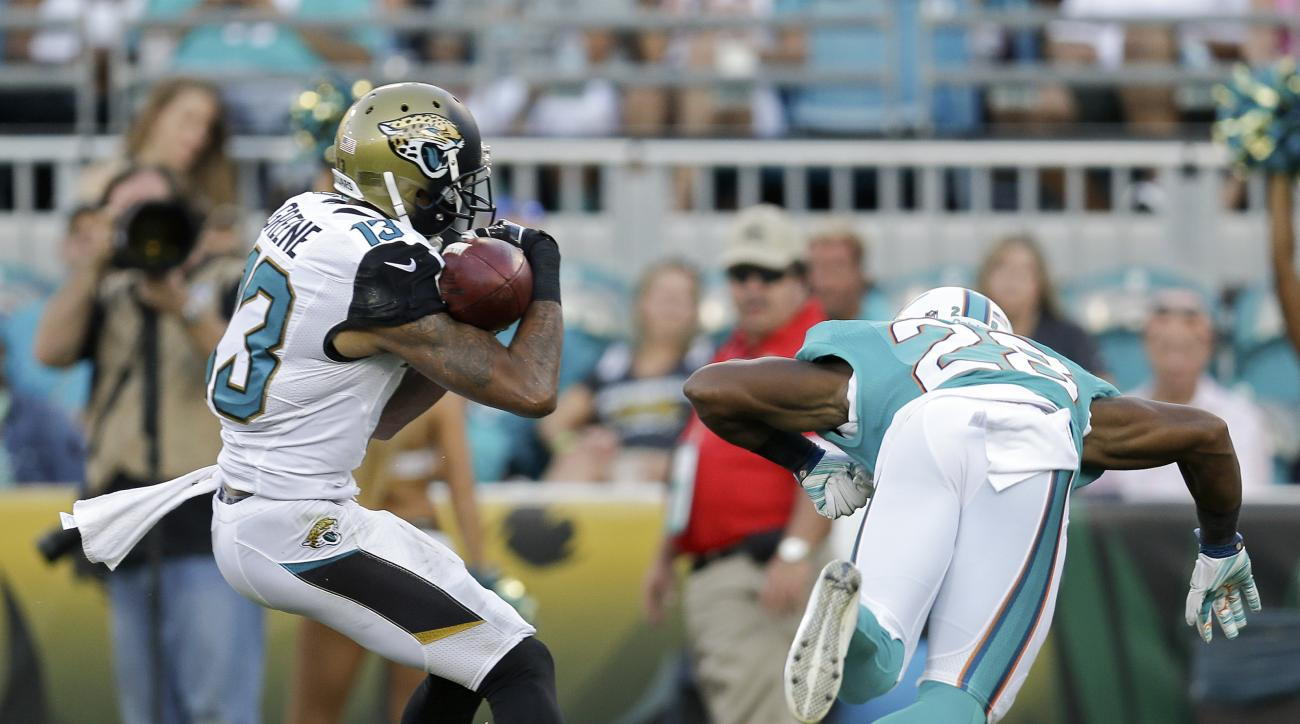 Jacksonville Jaguars wide receiver Rashad Greene (13) makes a reception in front of Miami Dolphins cornerback Bobby McCain, right, during the second half of an NFL football game in Jacksonville, Fla., Sunday, Sept. 20, 2015.(AP Photo/Mike Stewart)