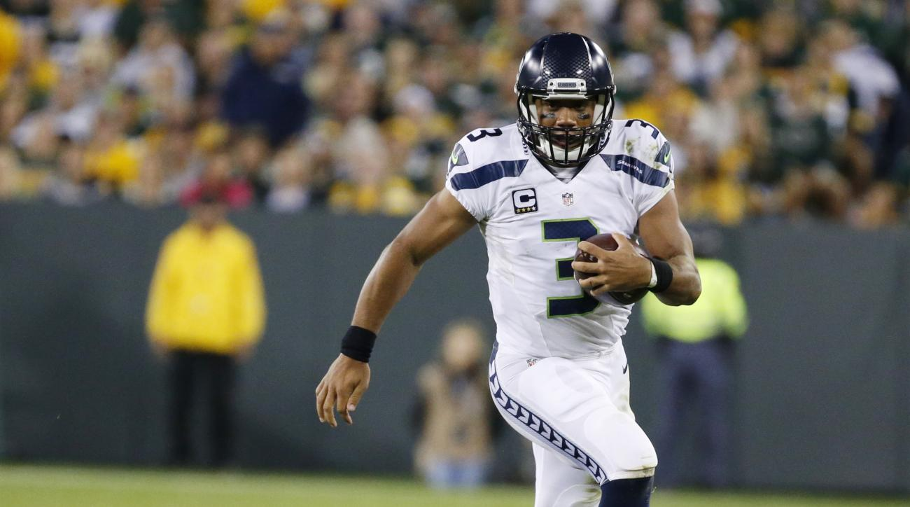 Seattle Seahawks' Russell Wilson runs past Green Bay Packers' Nick Perry during the second half of an NFL football game Sunday, Sept. 20, 2015, in Green Bay, Wis. (AP Photo/Mike Roemer)