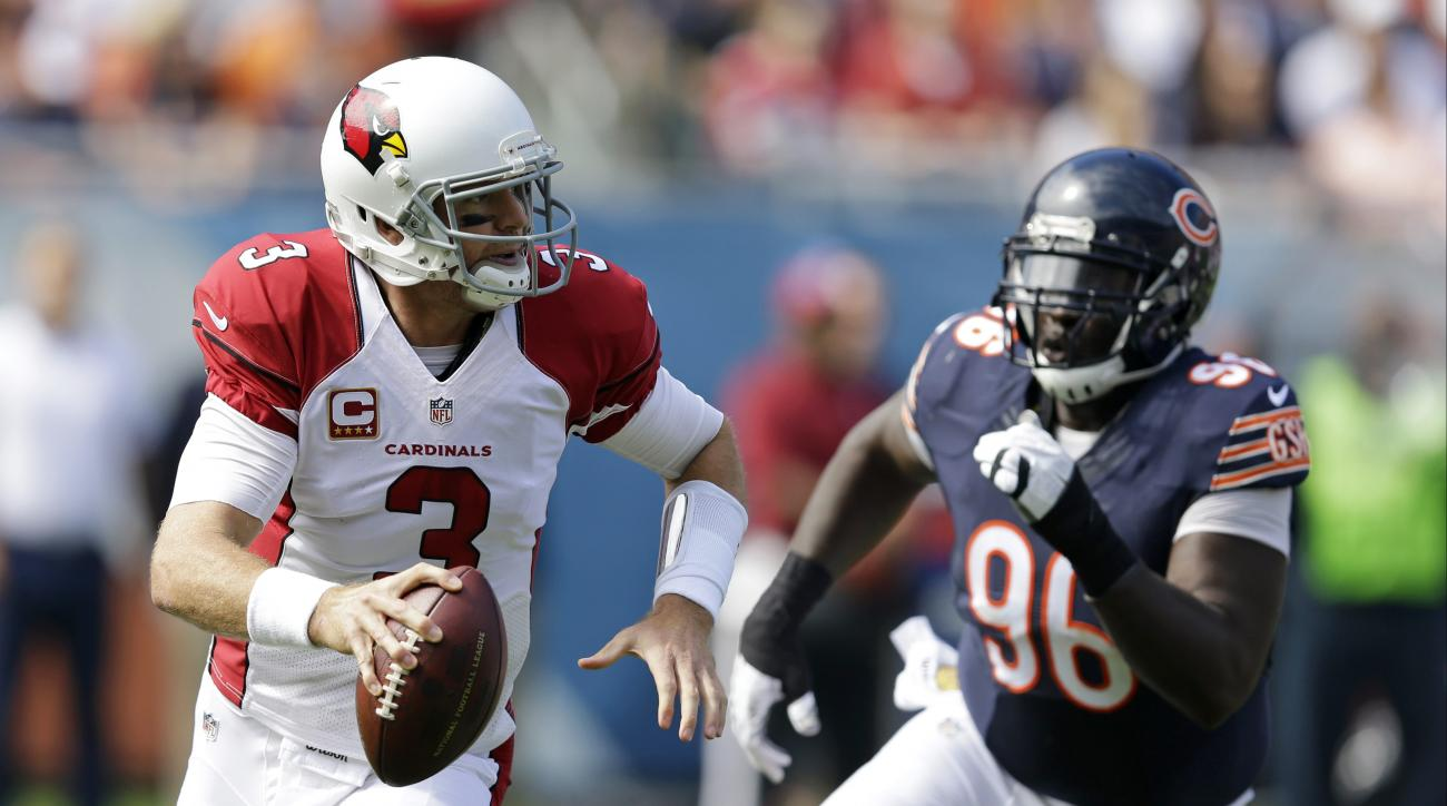 FILE - In this Sunday, Sept. 20, 2015 file photo, Arizona Cardinals quarterback Carson Palmer (3) scrambles away from Chicago Bears defensive tackle Jarvis Jenkins (96) during the first half of an NFL football game in Chicago. Palmer threw for four touchd