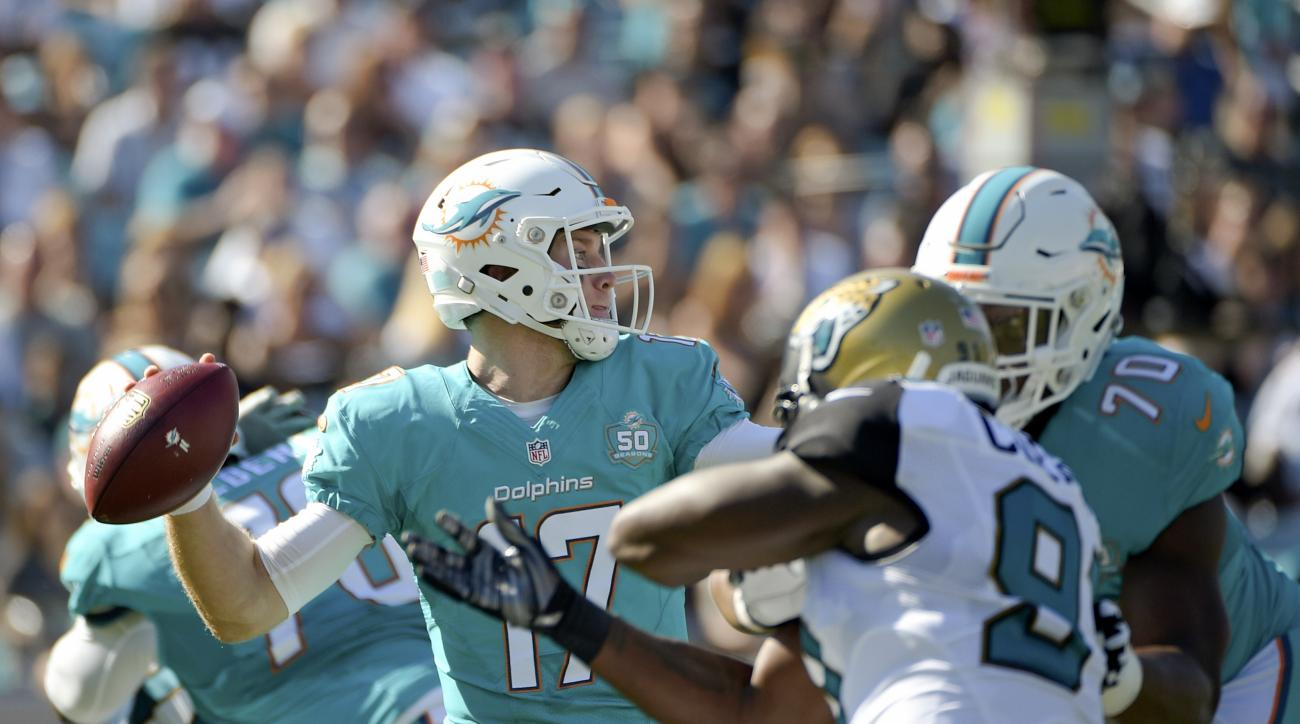 FILE - In this Sept. 20, 2015 file photo, Miami Dolphins quarterback Ryan Tannehill (17) throws a pass as he is pressured by Jacksonville Jaguars defensive end Chris Clemons left, during the first half of an NFL football game in Jacksonville, Fla. Injurie