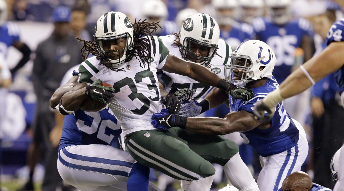 Indianapolis Colts inside linebacker Jerrell Freeman, bottom right, loses his helmet as he helps tackle New York Jets running back Chris Ivory (33) with Colts' outside linebacker Trent Cole (58) in the first half of an NFL football game in Indianapolis, M