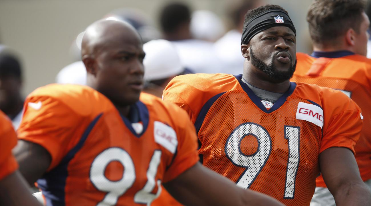 FILE - In this Thursday, Aug. 6, 2015 file photo, Denver Broncos defensive ends Kenny Anunike (91), right, and DeMarcus Ware (94) look on during drills at the team's NFL football training camp in Englewood, Colo. Anunike returned to practice in late Septe