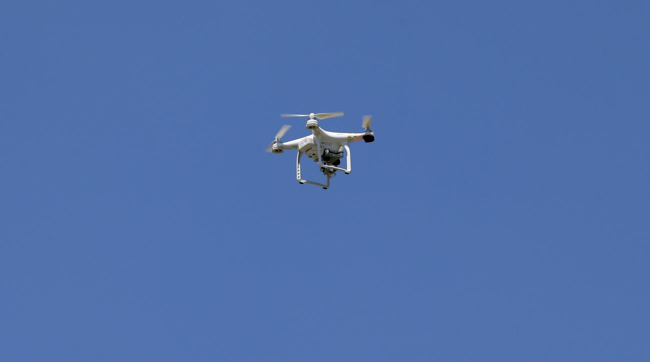 A drone hovers over the practice field during a Dallas Cowboys organized team activity at the NFL football team's headquarters, Wednesday, June 10, 2015, in Irving, Texas. The FAA is investigating the use of the drones by the Cowboys and two other NFL tea