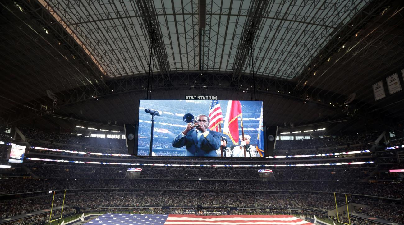In thiis Sept. 13, 2015, photo, U.S. service personnel unfurl a field-sized United States flag inside AT&T Stadium as trumpeter Freddie Jones, displayed on the giant video board, plays the national anthem before an NFL football game between the New York G
